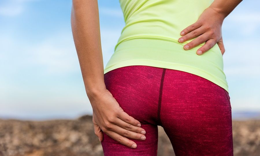 Lower back glute muscle pain cramp athlete runner. Running woman