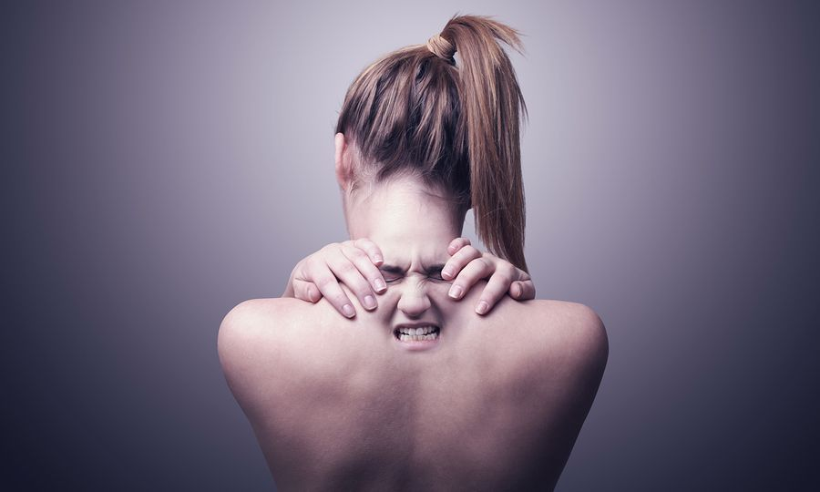 A nude back of a woman indicating neck pain